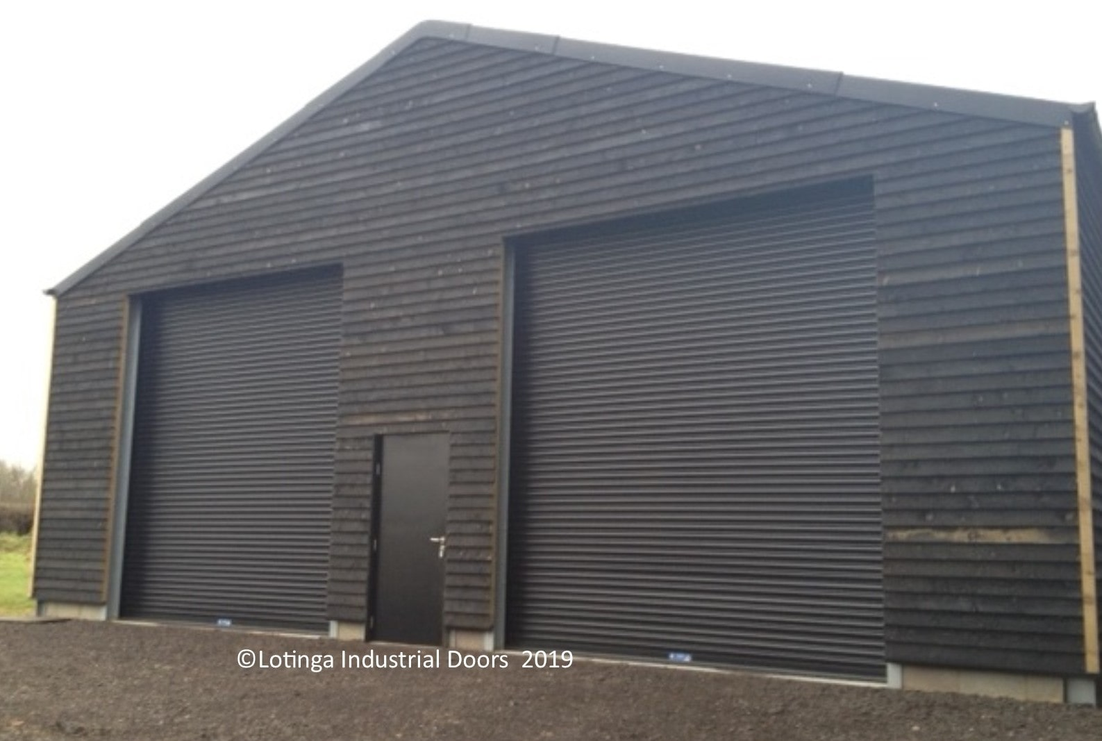 roller-shutter-on-barn-with-personnel-door-min Industrial Doors